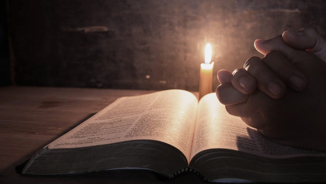 Rukoilevat kädet Raamatun päällä
