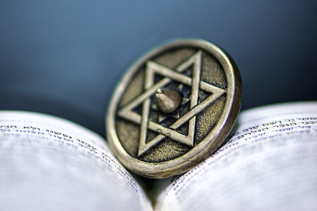 pinssi, jossa daavidin tähti, hepreankielisen kirjan keskellä.