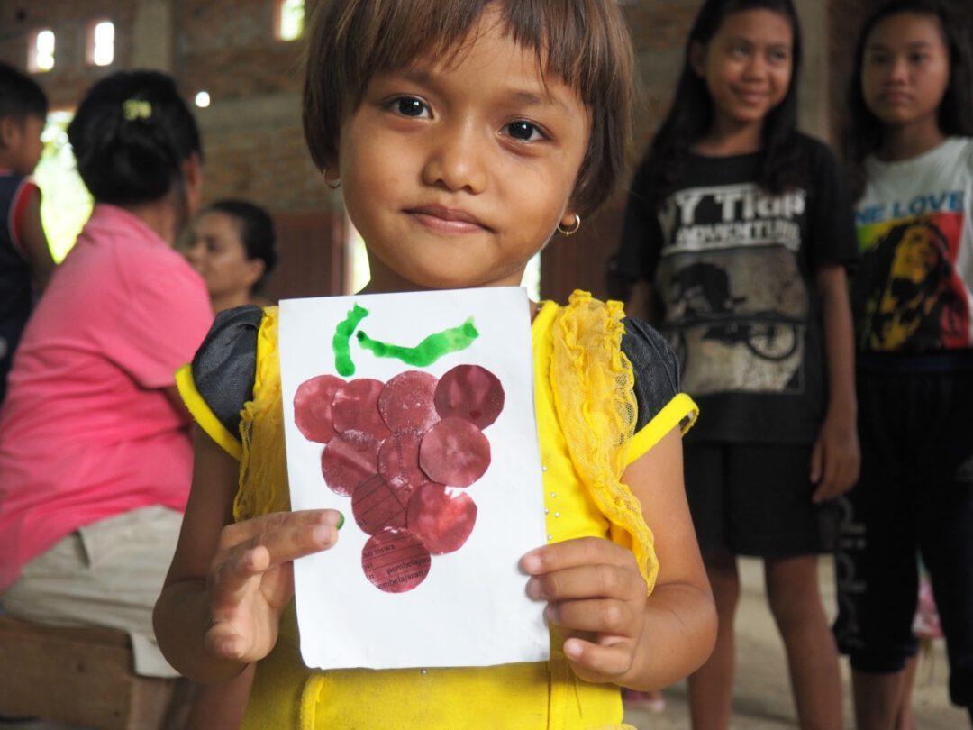 Lapsi pitää kädessään askarreltua kuvaa viinirypäleestä.